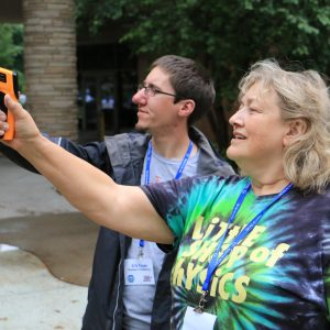 Two people standing outside use thermal radiation sensors (IR thermometers) to measure the temperature of a distant object. The person in the foreground is wearing a Little Shop of Physics tie-dye t-shirt. The person situated behind her is wearing a purple shirt and a raincoat. They are both looking at the distant object.